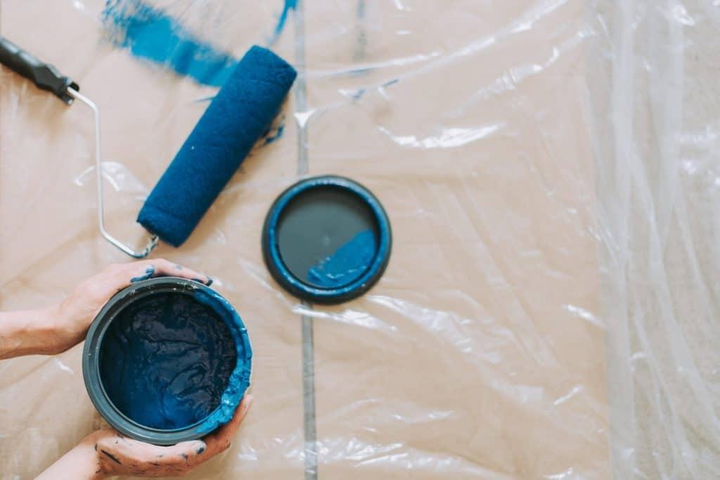 Imagem de rolo de espuma ao lado de tinta azul.