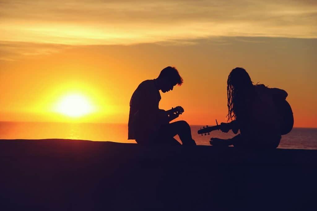 Duas pessoas tocando violão com capotraste em uma praia em pleno pôr do sol. Elas estão à direita da imagem. Na esquerda está o sol se pondo.