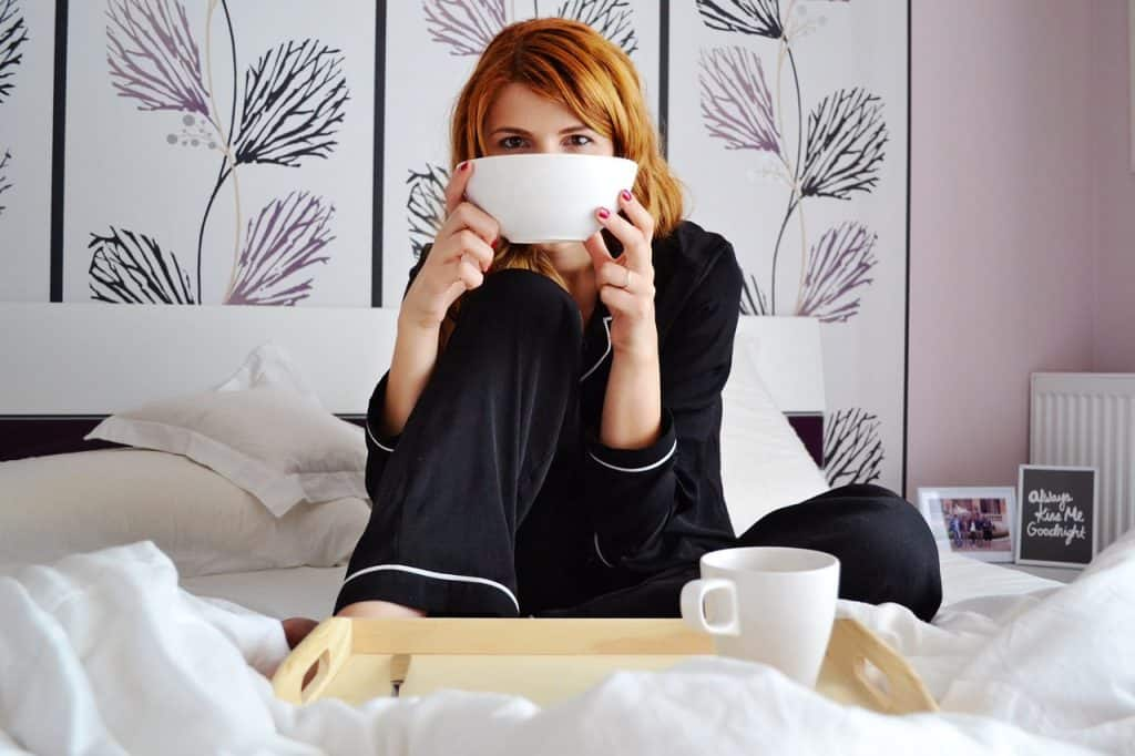 Na foto uma mulher sentada em uma cama tomando café da manhã.