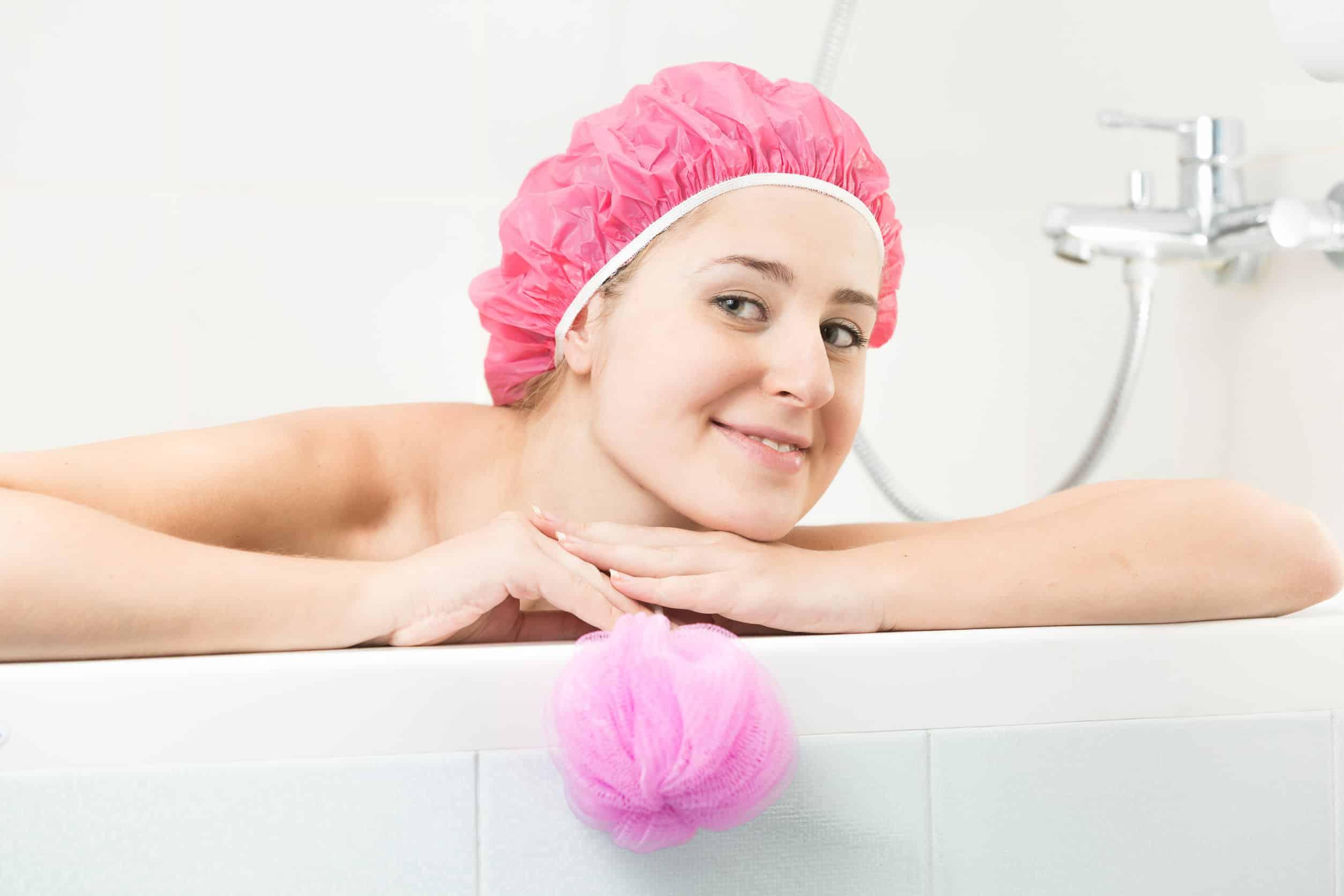 Imagem de mulher em banheira usando touca de banho.
