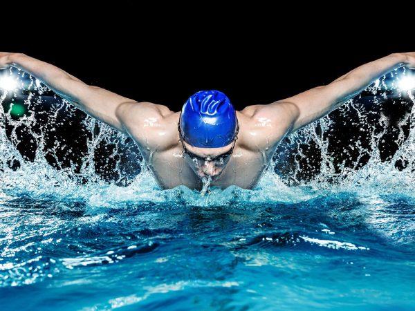 Imagem de homem nadando em piscina usando touca de natação azul.