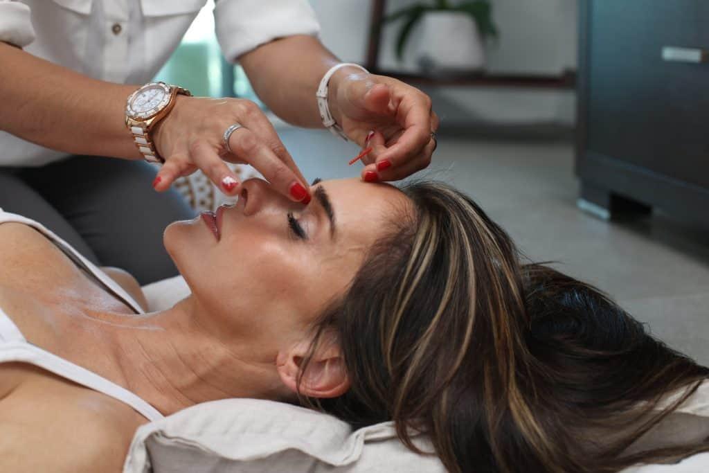 Imagem de uma mulher recebendo cuidados no rosto.