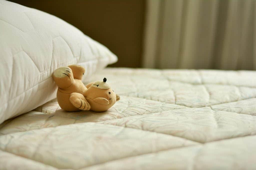 Foto de um pequeno urso de pelúcia perto de um travesseiro sobre a cama.