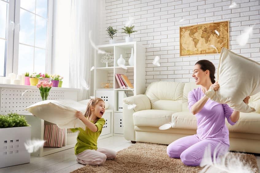 Imagem mostra mãe e filha fazendo guerra de travesseiro.