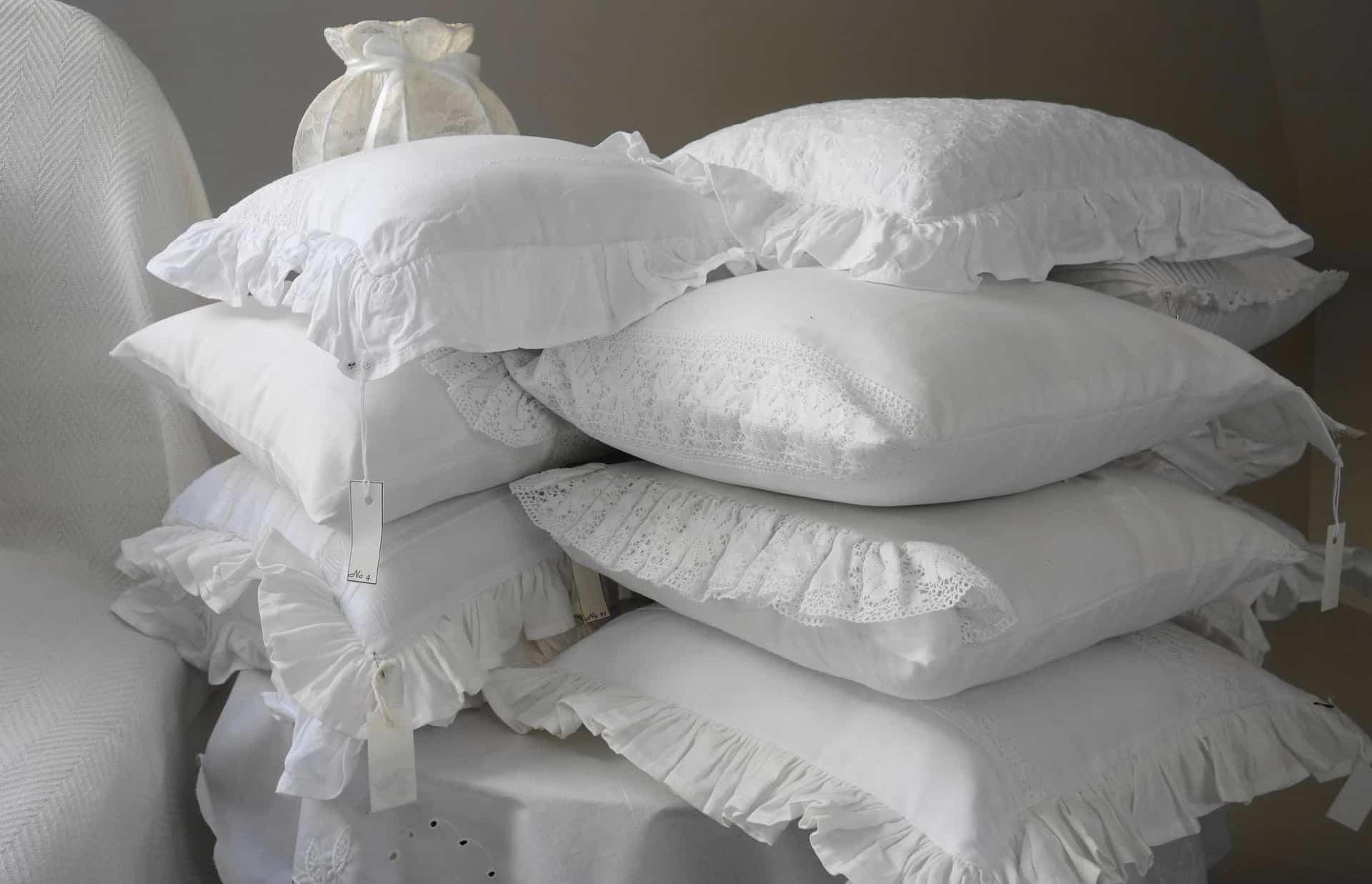 Imagem mostra uma pilha grande de travesseiros em fronhas brancas.