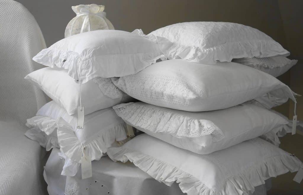 Vários travesseiros de tamanhos diferente empilhados.