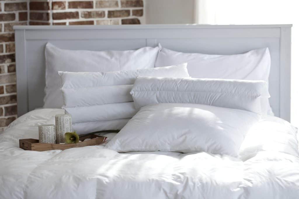 Cama com vários travesseiros.