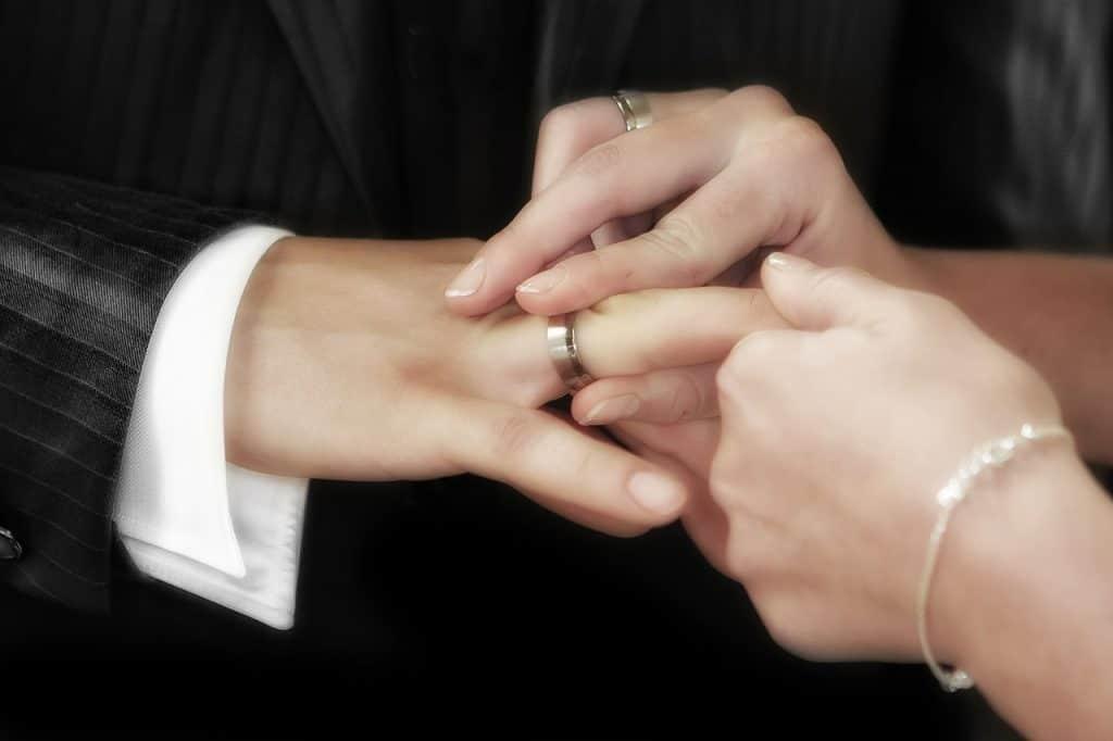 Mão de mulher colocando anel de compromisso na mão do homem.