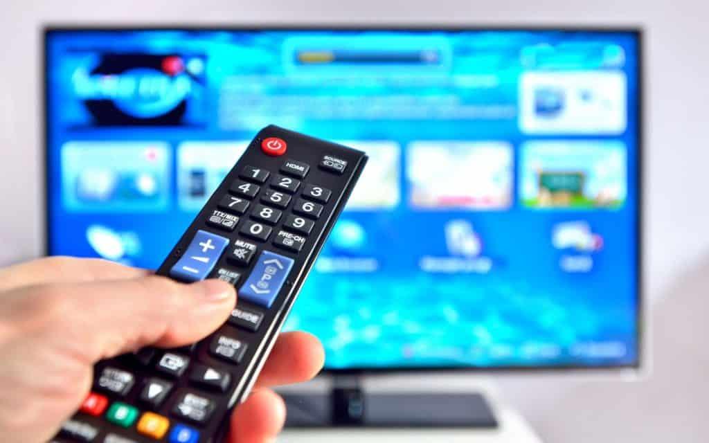 Televisão grande com controle na frente.