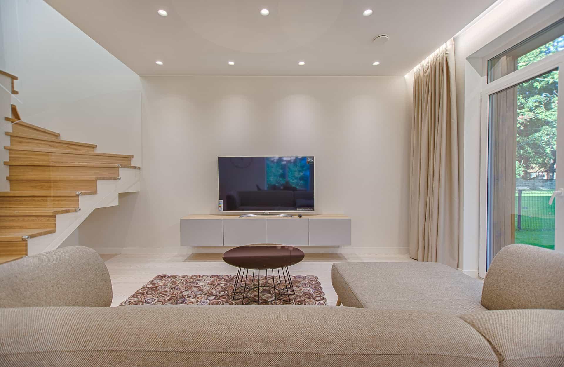 Na imagem há uma sala de estar com escada de madeira no canto esquerdo e uma grande janela no lado direito, no meio está uma televisão.