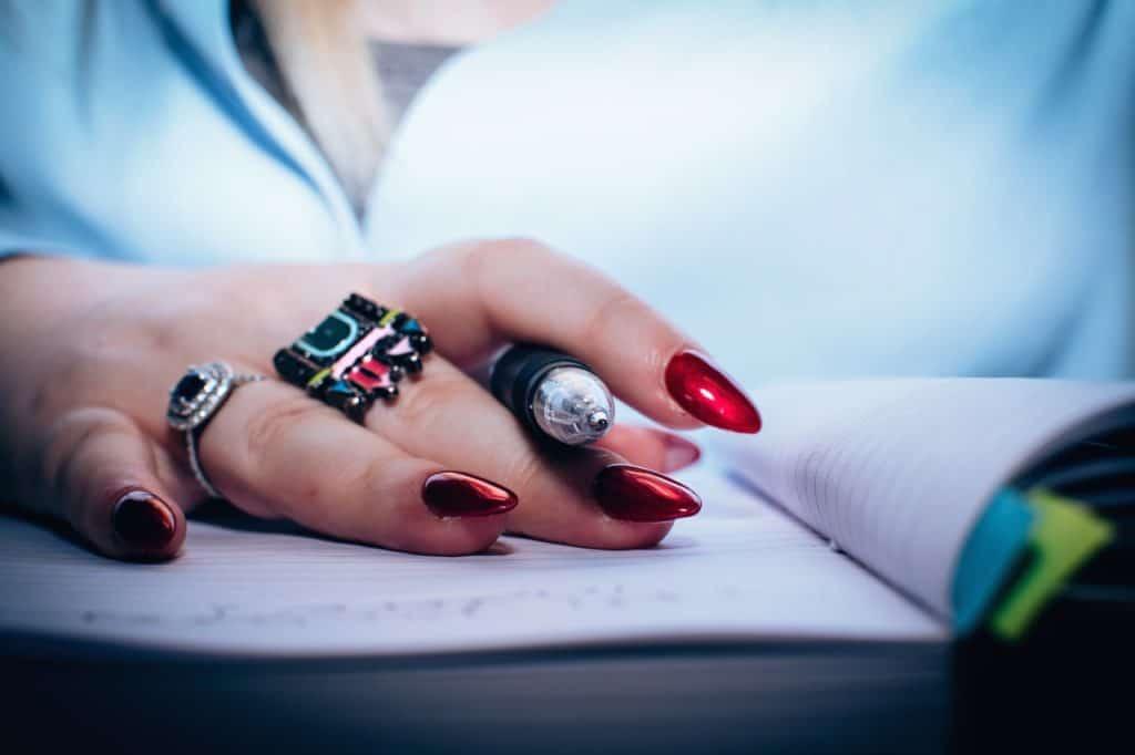 Foto das mãos de uma mulher em cima de um livro, segurando uma caneta entre os dedos. Ela possui dois anéis nos dedos e unhas vermelhas cintilantes.