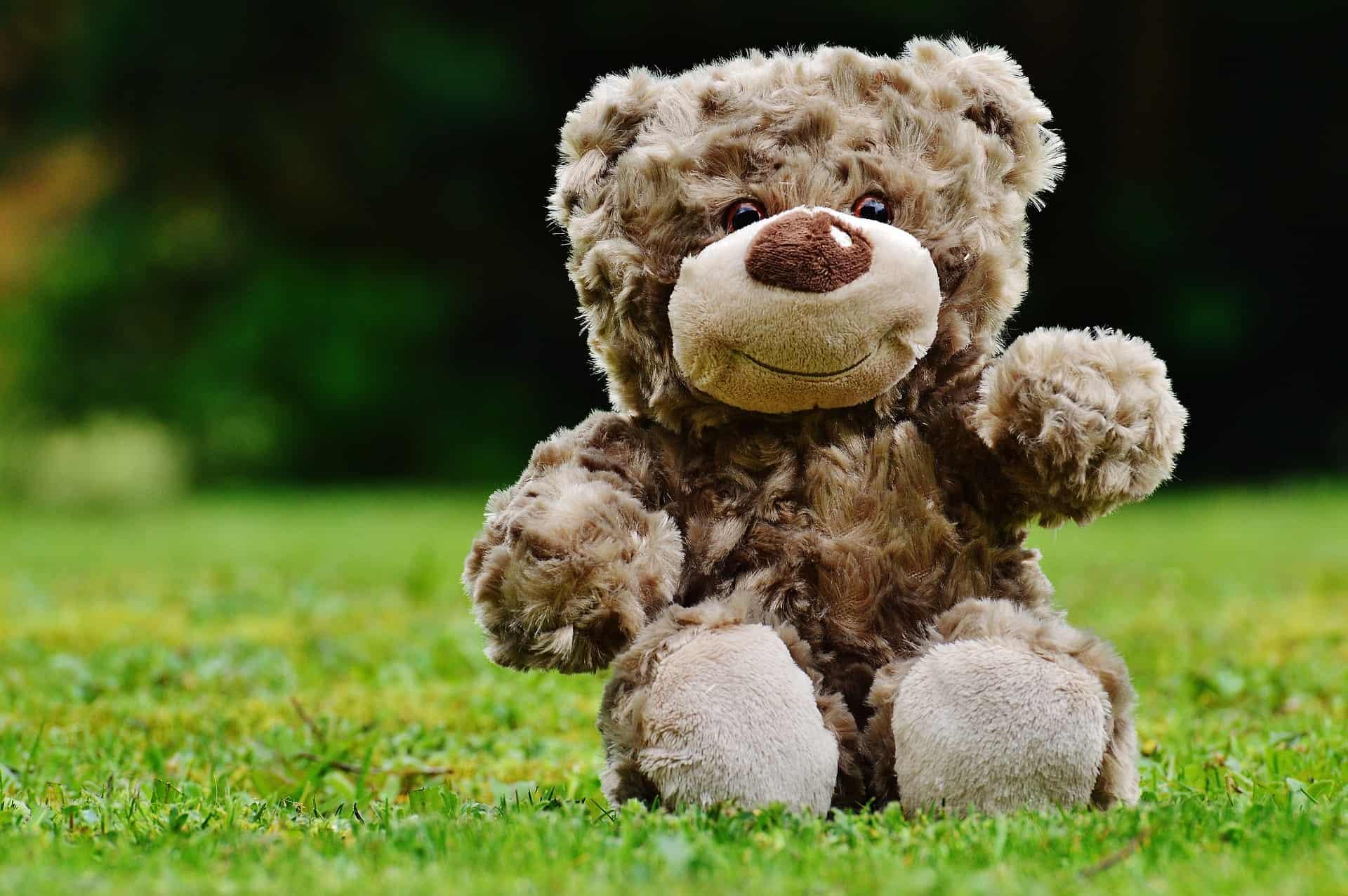 Urso de pelúcia gigante sentado na grama.
