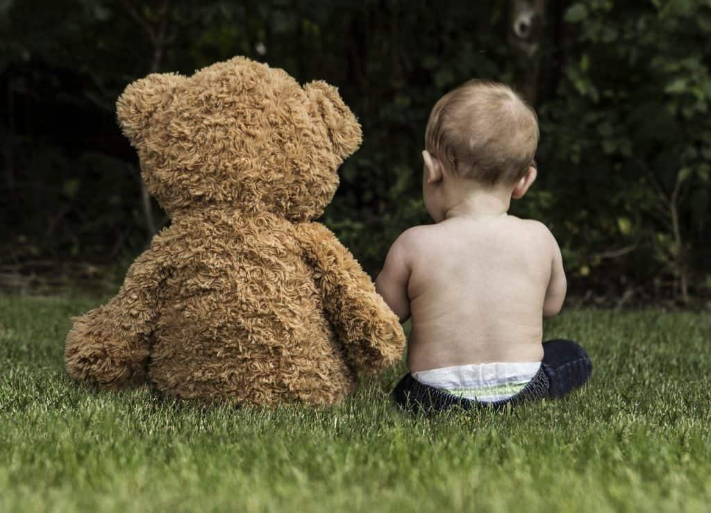 Bebê sentado de costas ao lado de urso de pelúcia gigante no gramado.