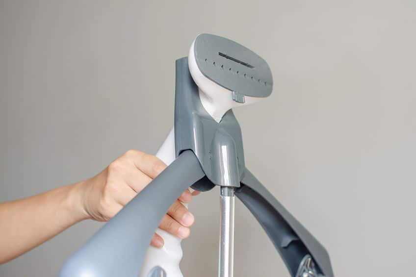 Imagem de uma mão usando um vaporizador de roupas profissional.