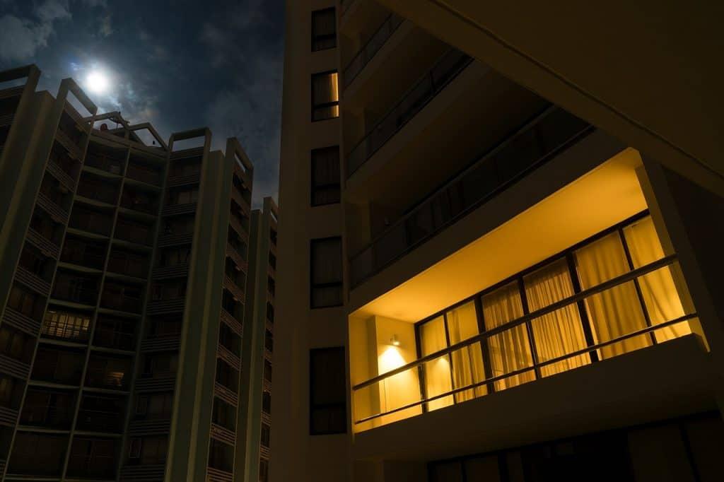 Varanda de apartamento iluminada por uma arandela.