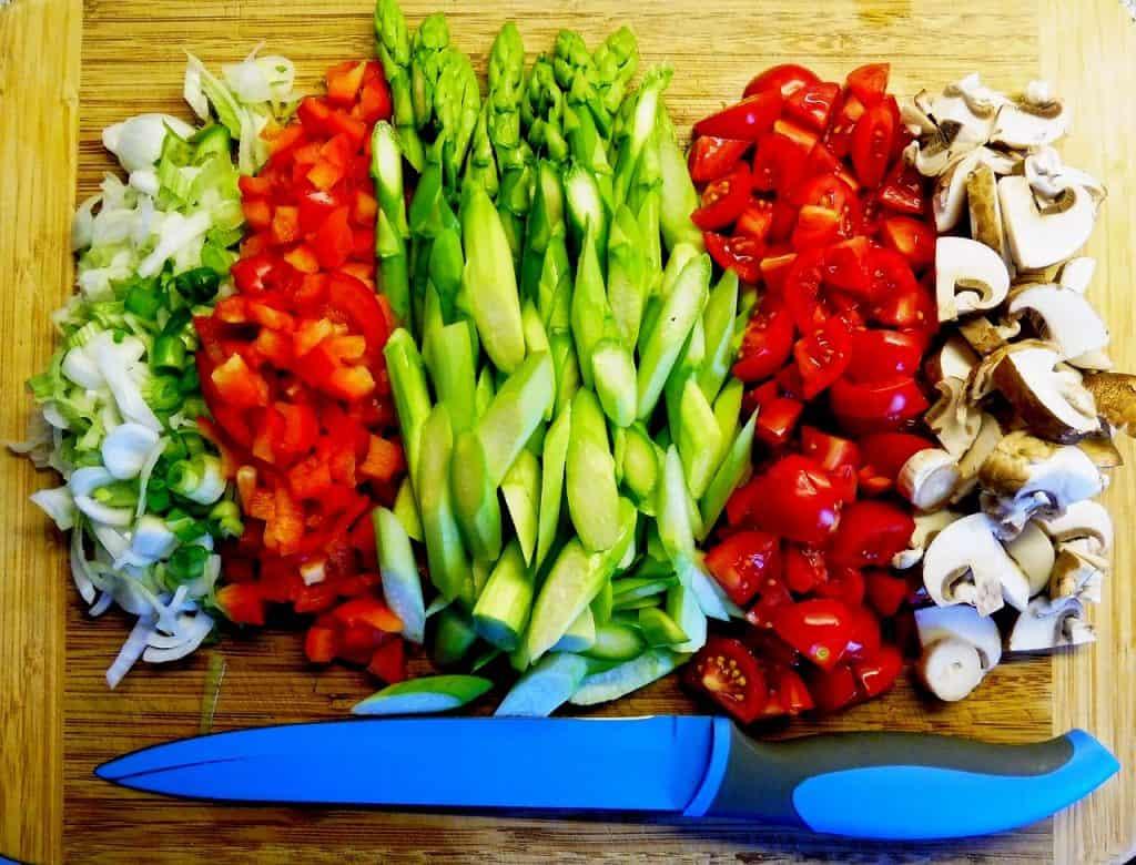 Imagem de vegetais cortados por uma faca de cerâmica azul.