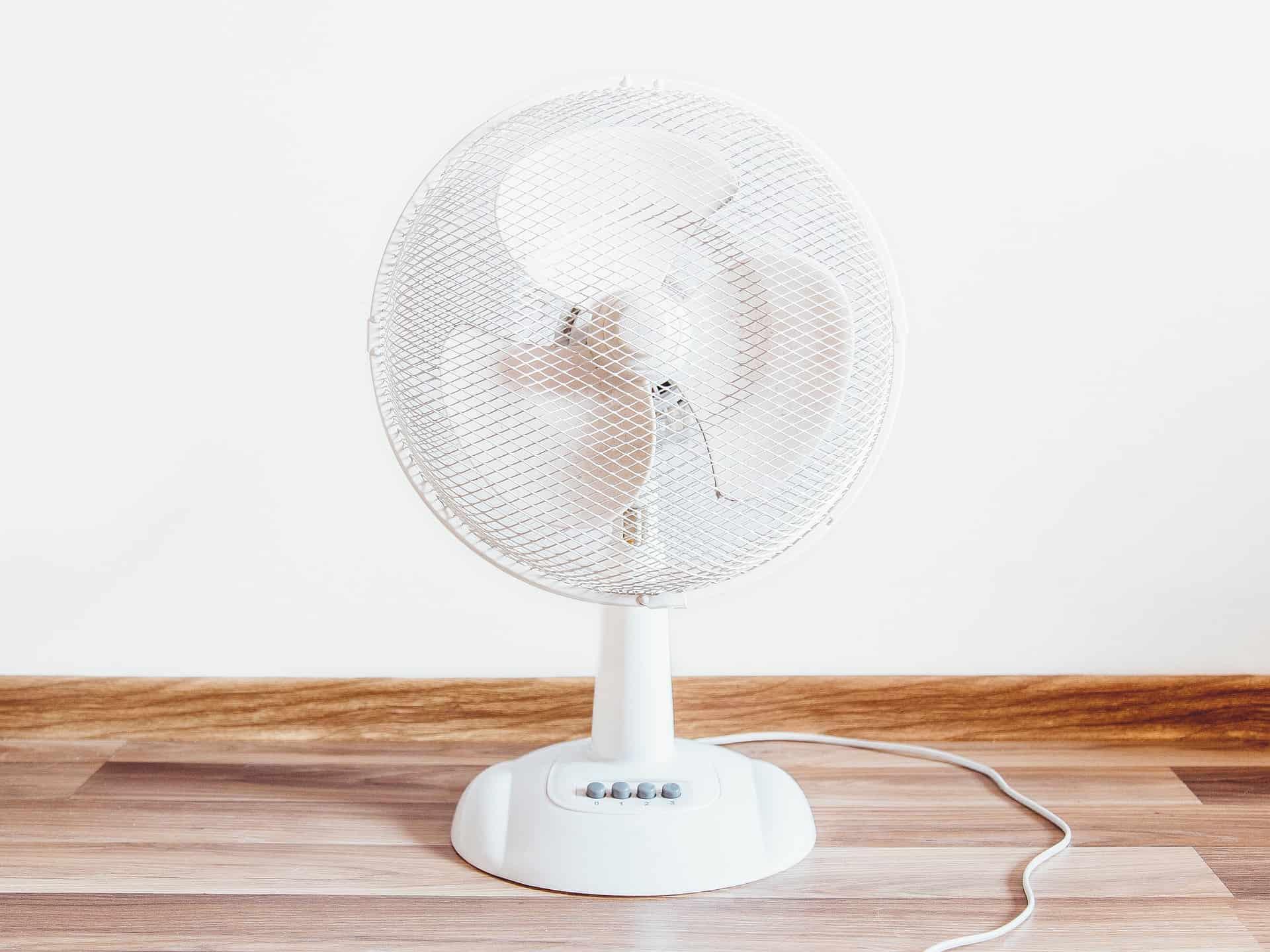 Foto de um ventilador branco, de três pás, no chão, com uma parede branca ao fundo.