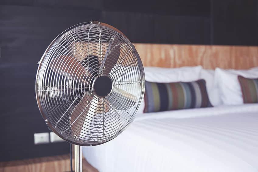 Imagem de ventilador prateado em quarto.