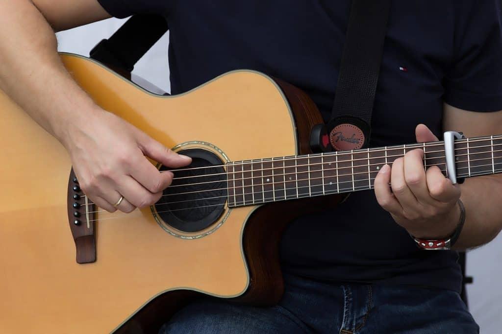 Uma pessoa com trajes masculinos tocando violão com capotraste. Na mão direita há uma aliança dourada. Existe um relógio no pulso esquerdo. A pessoa veste um jeans básico e uma camiseta escura. O violão está posicionado na coxa direita, à esquerda de quem vê a imagem.