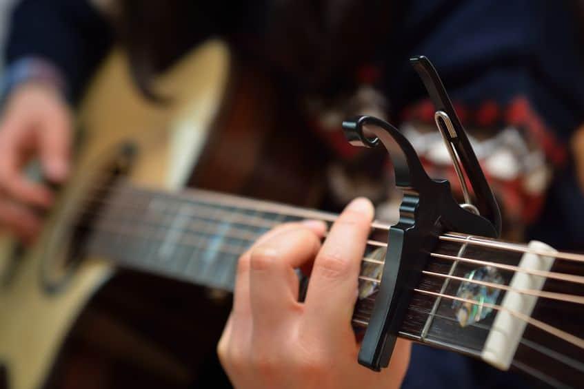 Um capotraste fixado no braço de um violão.