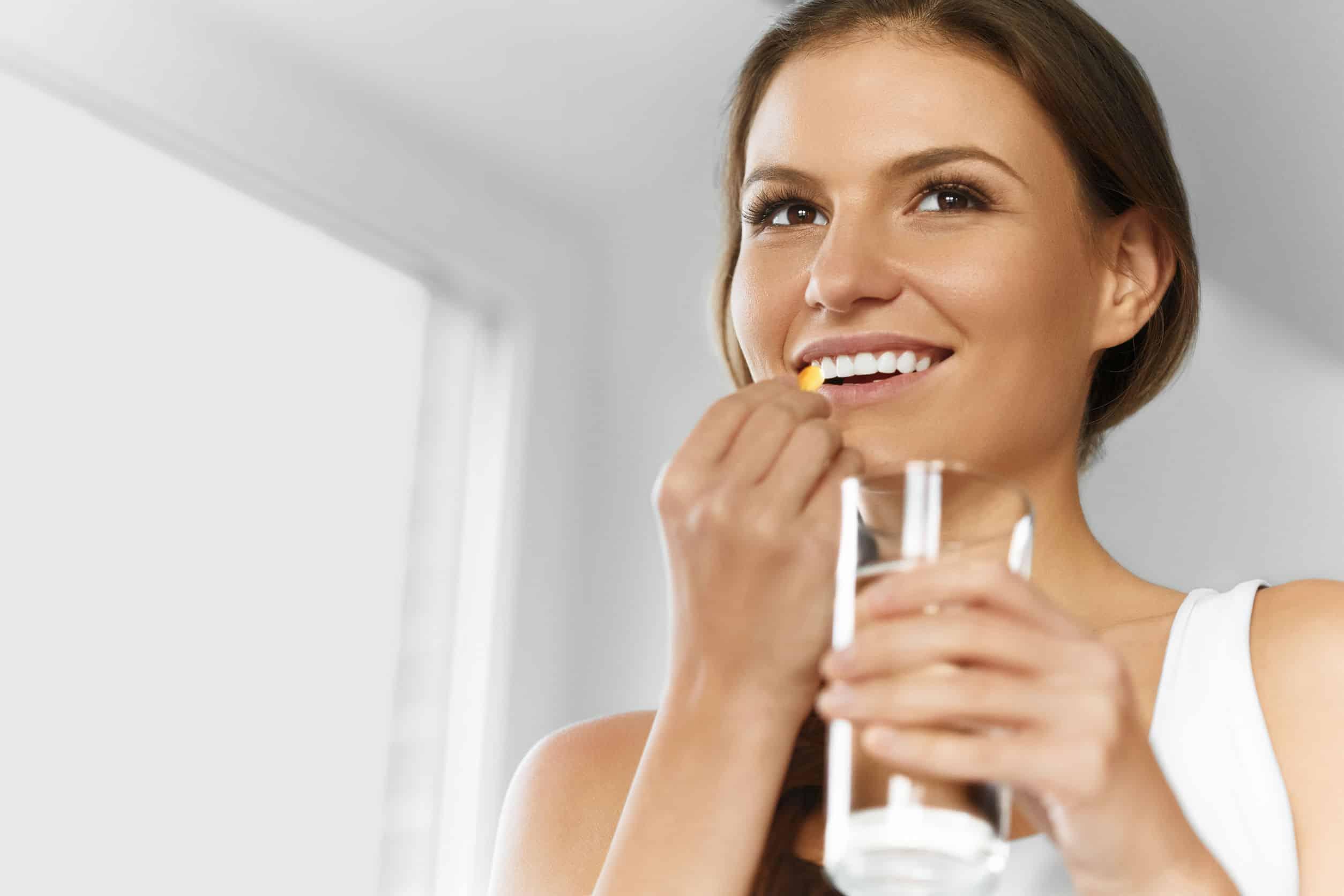 Mulher jovem pronta para ingerir cápsula de vitamina D.