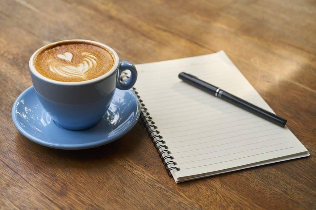Xícara de café com caderno e caneta ao lado.