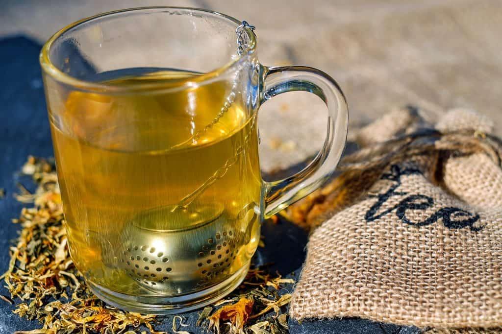 Imagem de infusor de metal em caneca de vidro sobre mesa de folhas de chá seco e saco de pano.