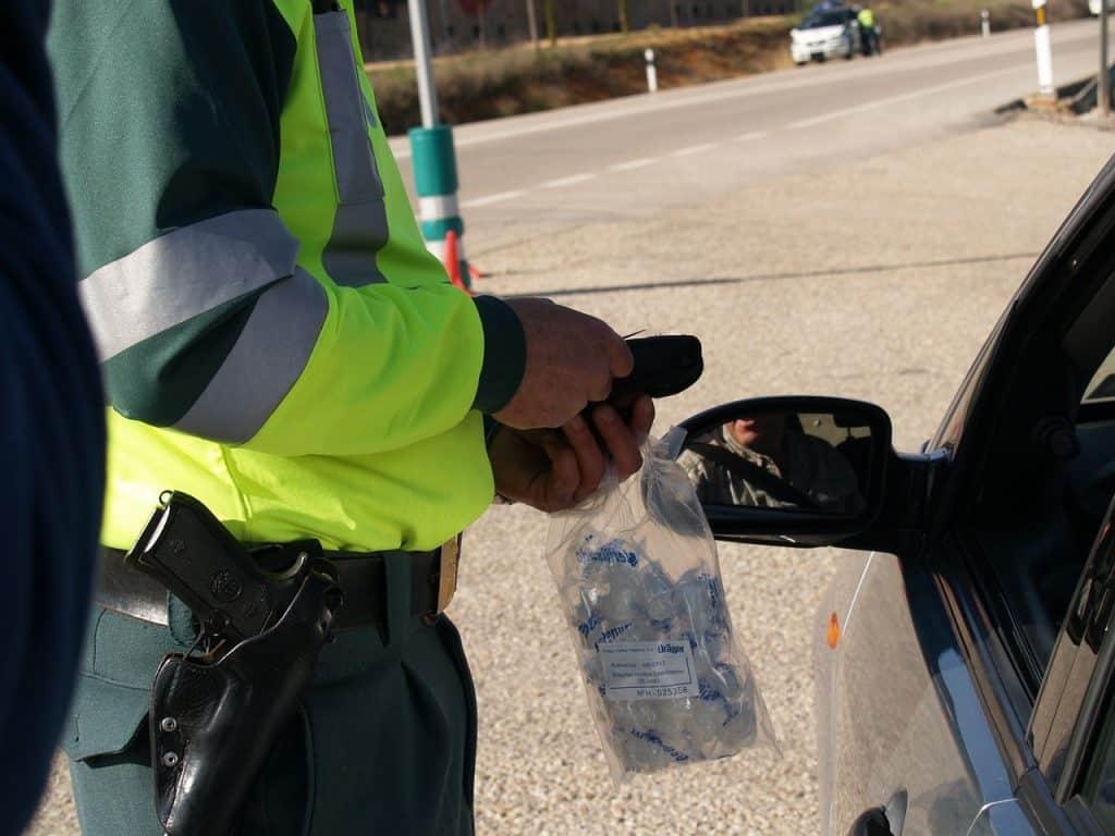 Guarda de trânsito lendo a medição auferida pelo bafômetro em suas mãos. Ao lado um motorista sentado em seu carro aguarda.