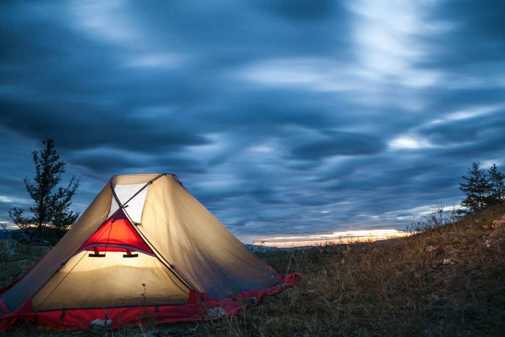Barraca iluminada em acampamento.