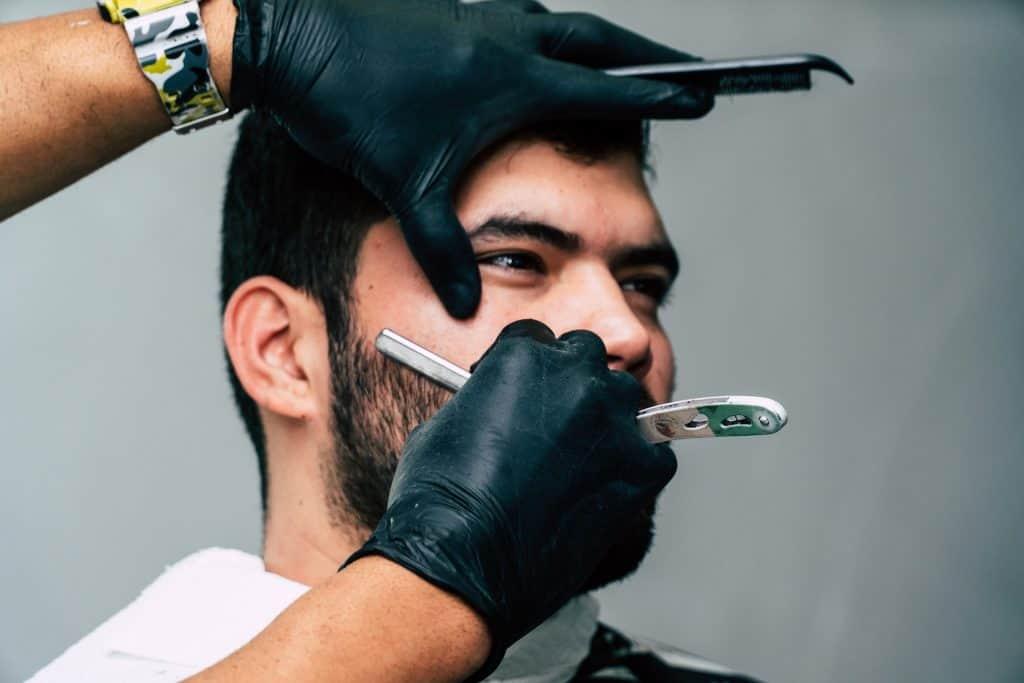 Imagem mostra uma pessoa usando uma navalha para barbear o rosto de um homem.
