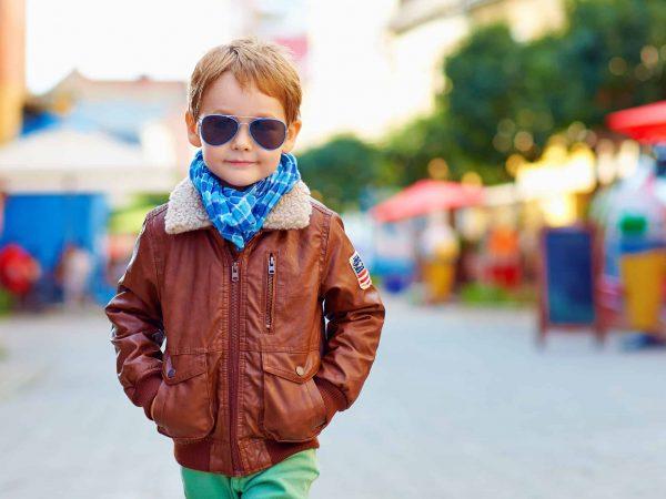 Na foto um menino usando jaqueta de couro marrom, calça verde e óculos escuros.