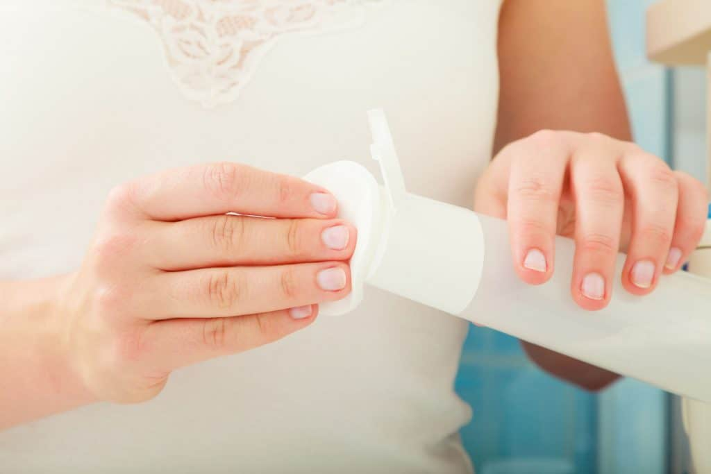 Mãos colocando água do tubo no algodão.
