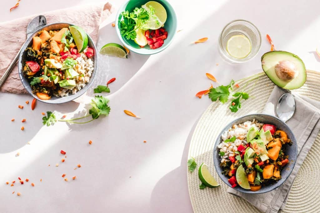Na foto há três recipientes com variadas frutas e legumes em cima de uma toalha branca. A foto foi tirada de cima e é possível ver um copo e duas colheres junto com a comida.