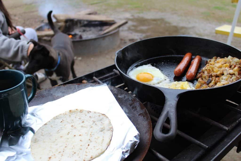 Imagem mostra fogão rústico ao ar livre onde uma refeição de ovos com linguiça e bacon é preparada em uma frigideira de ferro.