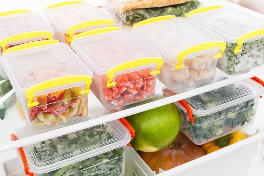 Na foto uma geladeira aberta com alimentos dentro.