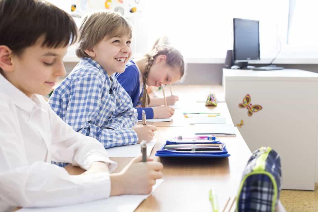 Garotos em sala de aula com estojo na mesa.