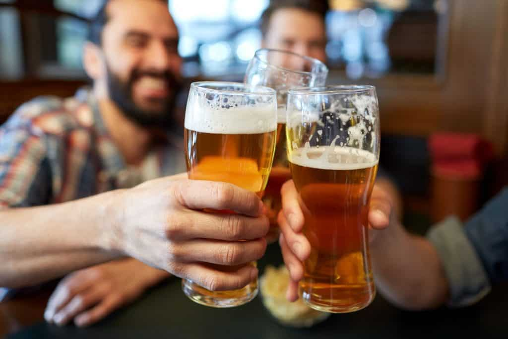 Imagem mostra um grupo de amigos brindando com cerveja.