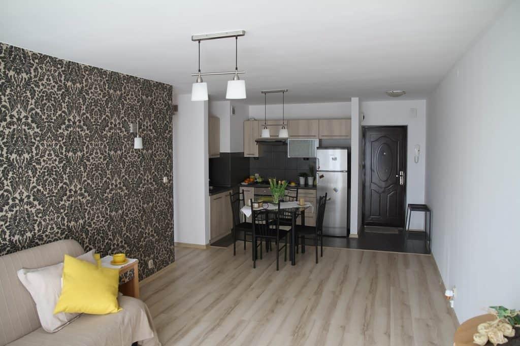 Imagem de cozinha em apartamento com geladeira pequena de inox.