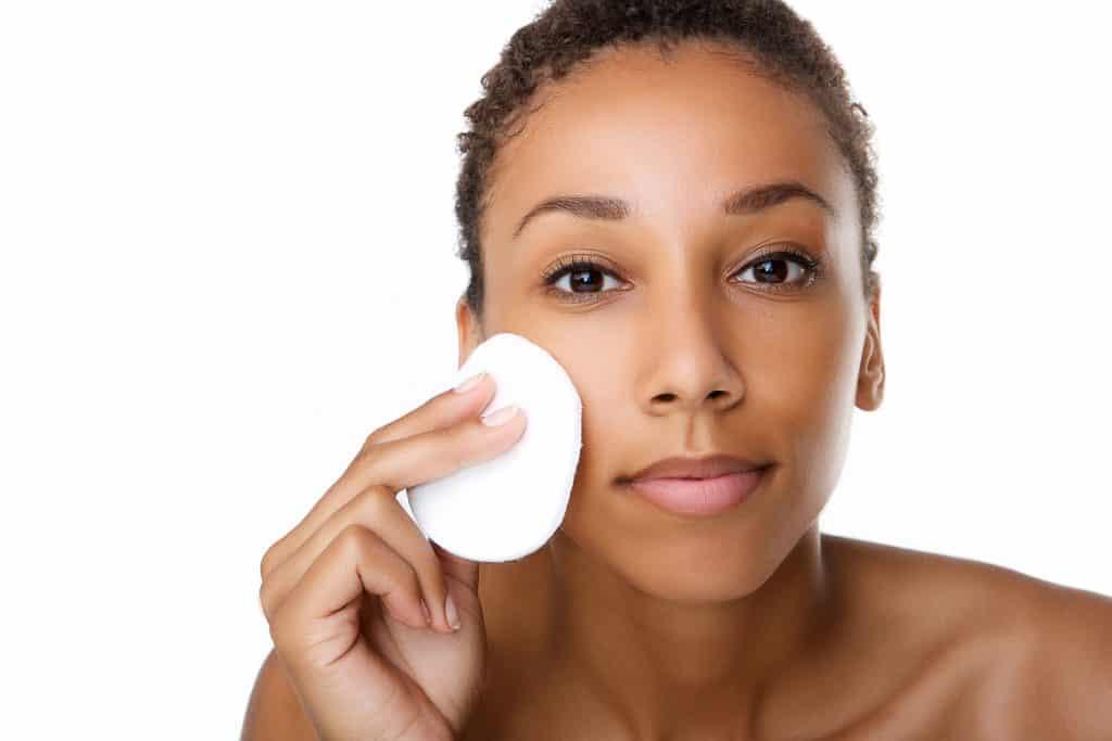 Mulher limpando o rosto com algodão.