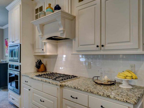 Cozinha em estilo clássico com armários em madeira na cor branca.