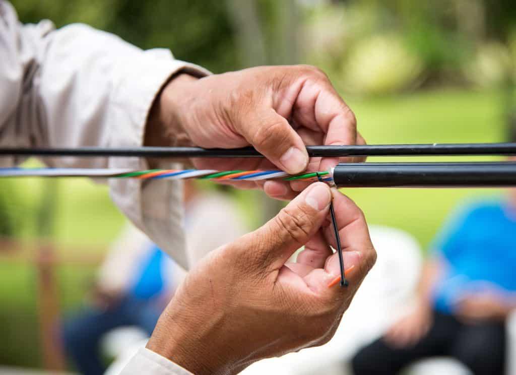 Homem fazendo instalação usando cabo óptico.