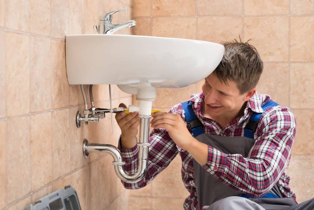 Um homem instalando um sifão de metal no banheiro.