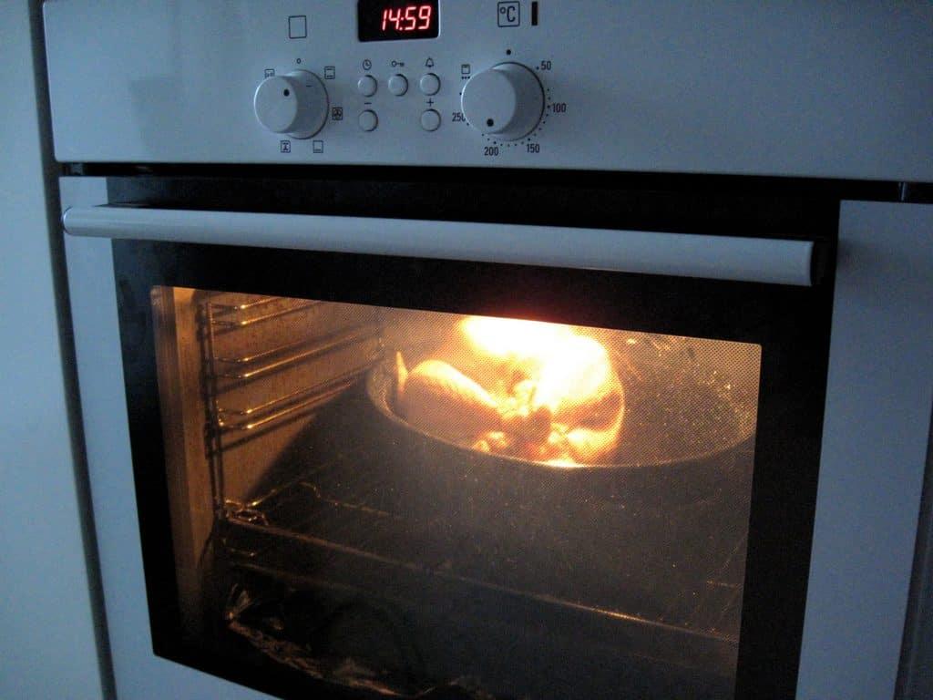 Imagem mostra um forno branco com a luz acesa e um peru assando na parte de dentro.
