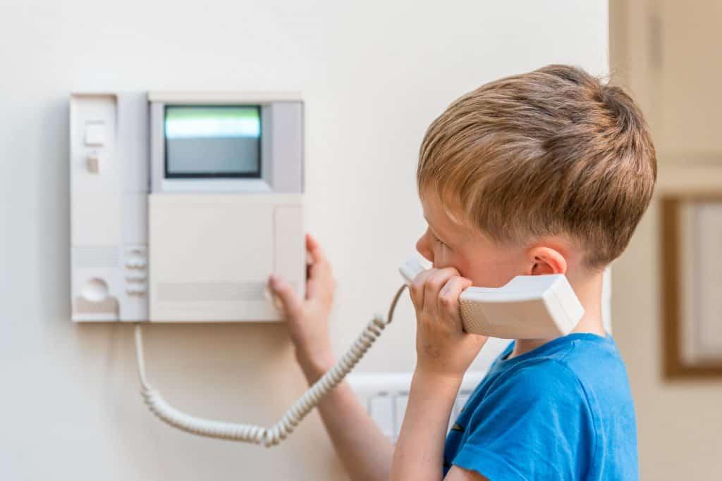 Imagem de menino atendendo interfone.