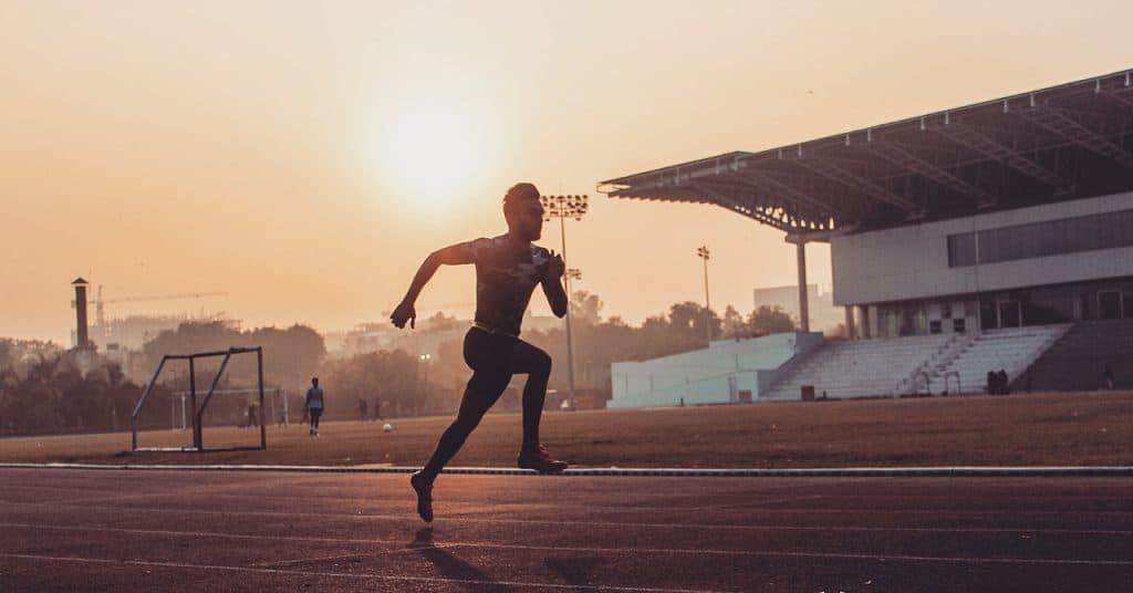 Na foto um homem correndo em uma pista de corrida com um campo de futebol ao fundo.
