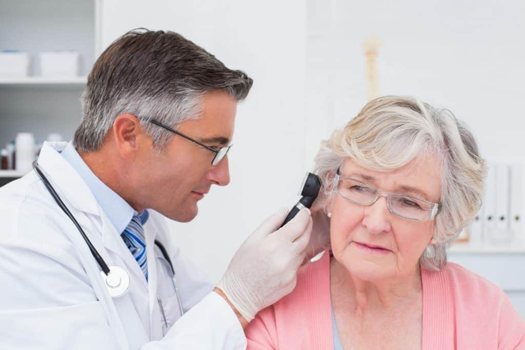 Médico analisando o ouvido de uma senhora.