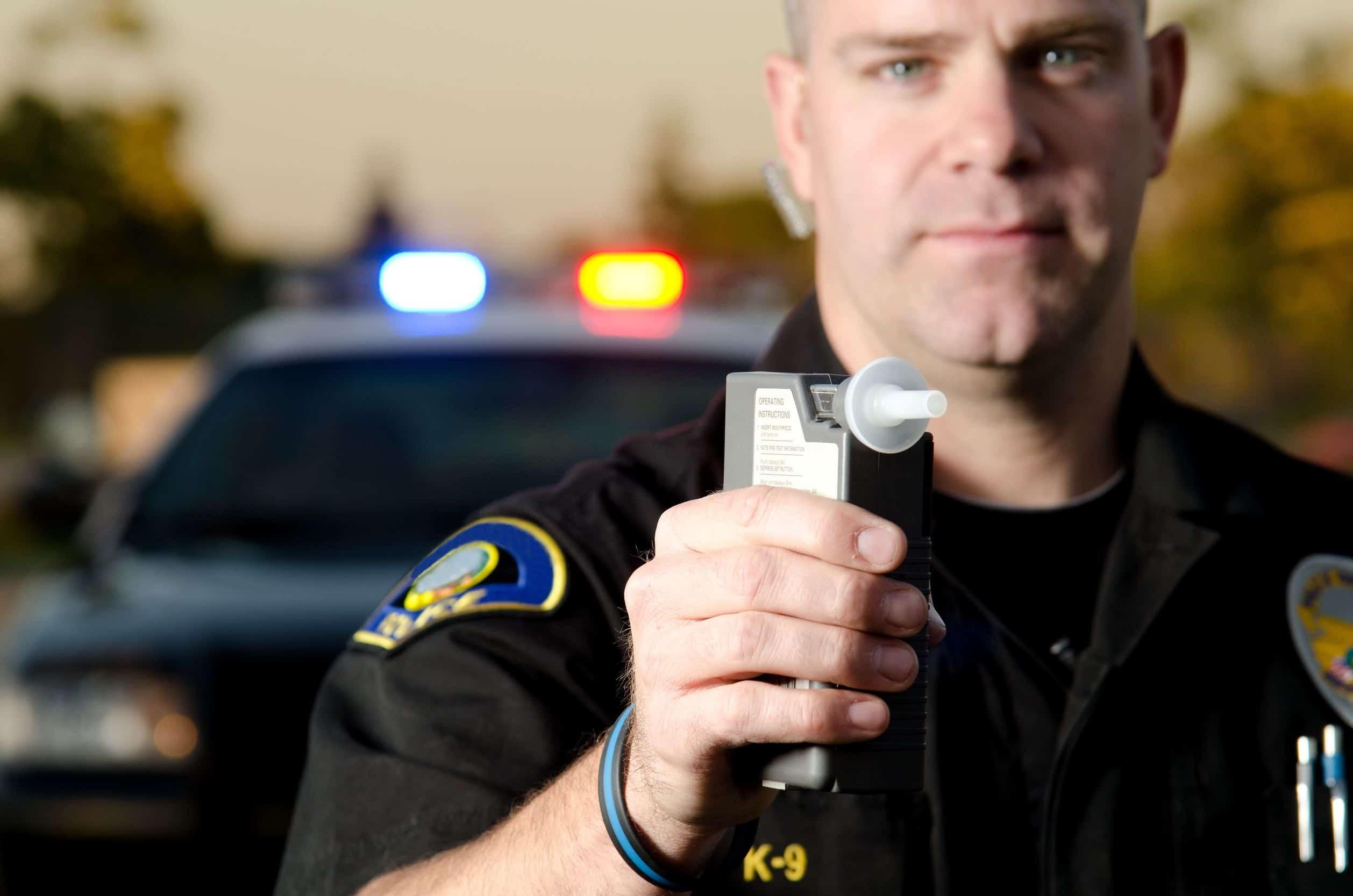 Imagem de policial segurando bafômetro.
