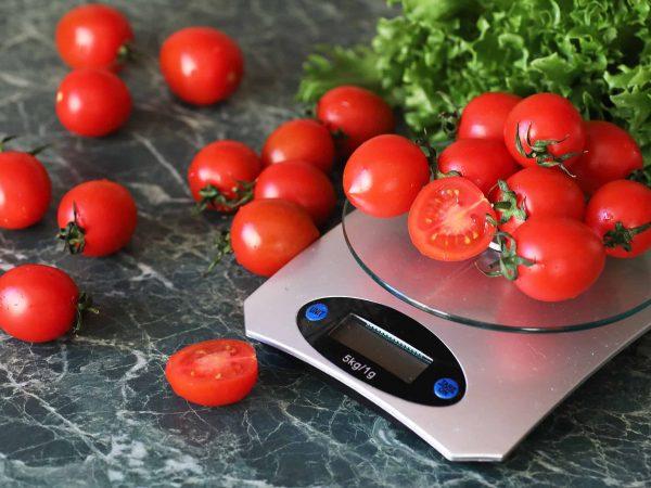 Na foto uma balança com tomates cereja em cima e ao redor.