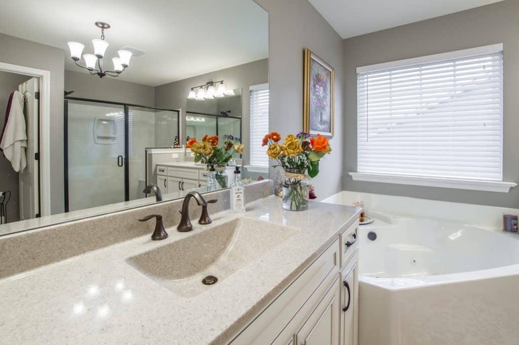 Na foto um banheiro todo branco e cinza, com uma banheira no canto.