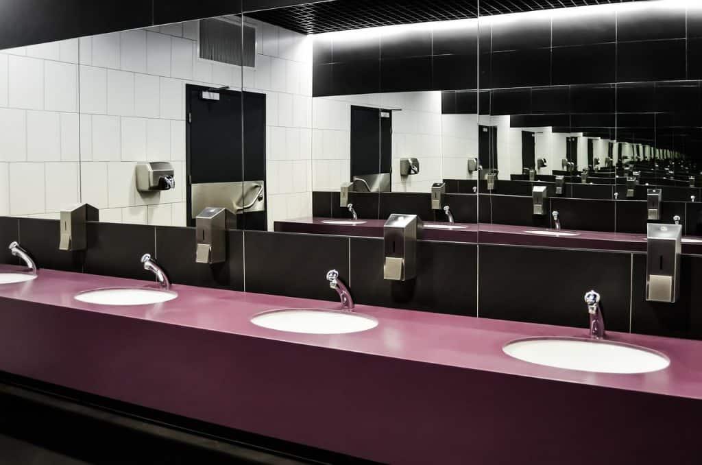 Uma pia de banheiro com quatro espelhos e quatro torneiras fechadas com sifões escondidos.